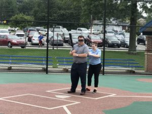 Nicole Meier helps Pat Dougherty in simulating what it would be like to play baseball with the disability of blindness. In this photo, Dougherty is getting ready to attempt to hit a beeper ball while he is unable to see.