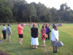 Guests at the event watch campers sing and recite the Pledge of Allegiance.